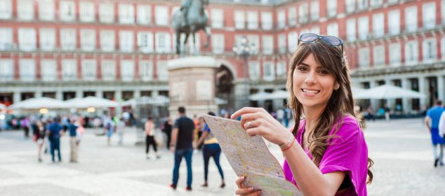 Young woman tourist holding a paper map in Plaza Mayor square, Madrid, Spain, looking at buildings. Tourist attraction, statue of Felipe III in the background.