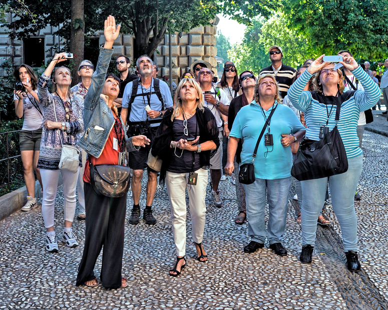 Granada, Spain - September 19, 2015: A female tour guide indicates a point of interest to a group of adult male and female visitors in Granada, Spain, some engaged in photographing.